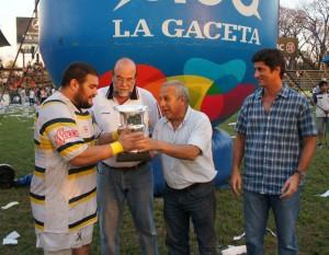 El presidente de la URT, Fernando Martoni entrega  la Copa al  jugador Álvaro Fernández
